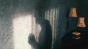 Sombra terrível em uma sala escura gótico ao lado de uma lâmpada do amarelo do vintage, sinistramente manejo Um fantasma ou uma b filme