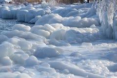 Sombras azules en el hielo a lo largo de la orilla Fotos de archivo