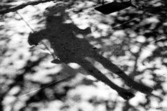 Sombras de Bluury de una persona en un oscilación Foto de archivo libre de regalías