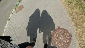 Sombras de dos amigos, mujeres que caminan en la calle en verano almacen de metraje de vídeo