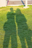 Sombras de la gente de los gemelos que lleva a cabo las manos en el jardín fotos de archivo