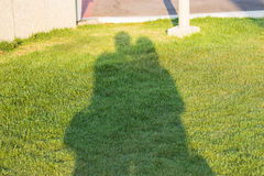 Sombras de la gente de los gemelos que lleva a cabo las manos en el jardín imagen de archivo libre de regalías