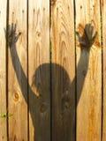 Sombras de la mano adolescente que aumentan para arriba en la cerca Fotografía de archivo libre de regalías