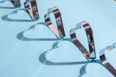Sombras de las formas del metal bajo la forma de corazón en azul imagenes de archivo