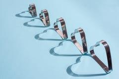 Sombras de las formas del metal bajo la forma de corazón en azul fotografía de archivo