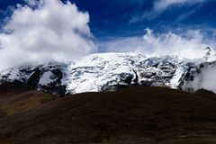 Sombras de las nubes de la baja altitud en un pico de montaña Himalayan nevado imagen de archivo libre de regalías