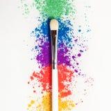 Sombras de ojos brillantes en diversos colores del arco iris y de los cepillos para los cosméticos en un fondo blanco imagenes de archivo