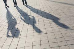 Sombras de tres amigos en el pavimento foto de archivo