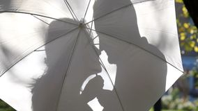 Sombras dos amantes que acariciam atrás do guarda-chuva video estoque