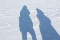 Sombras dos povos na neve imagens de stock