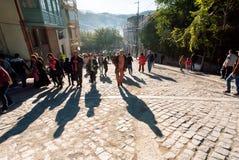 Sombras em pedras cobbled dos povos de pressa durante o festival Tbilisoba da cidade Fotografia de Stock Royalty Free