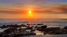 Sombras en colores pastel del reflejo del amarillo, rojo y azul en el océano en el sol poniente con las rocas en la playa fotografía de archivo libre de regalías