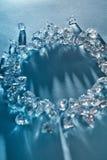 Sombras largas y reflexiones de los pedazos transparentes de cubos de hielo machacados en la forma redonda en un fondo azul con foto de archivo libre de regalías
