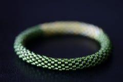 Sombras moldeadas hechas a mano de la pulsera dos del verde en un fondo oscuro fotografía de archivo