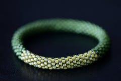 Sombras moldeadas hechas a mano de la pulsera dos del verde en un fondo oscuro fotos de archivo