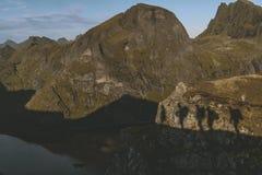 Sombras na montanha de um grupo de alpinistas que escalam a montanha no nascer do sol em Lofoten, Noruega fotos de stock