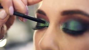 Sombras verde-clara de aplicação extremamente próximas do brilho no canto do olho Modelo caucasiano bonito filme