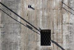 Sombras y ventana en muro de cemento