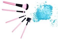 Sombreador de ojos azul machacado con el cepillo del maquillaje en el fondo blanco Foto de archivo