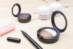 Sombreador de ojos de los cosméticos en la tabla de madera Fotos de archivo