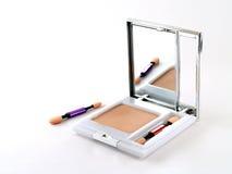 Sombreador de ojos del polvo del maquillaje y mini cepillo colorido de la esponja en caja con el espejo en el fondo blanco Imágenes de archivo libres de regalías