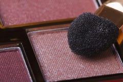 Sombreador de ojos en tonos rosados y primer del aplicador. Imagen de archivo