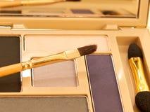 Sombreadores de ojos púrpuras y beige de lujo del maquillaje en el embalaje del oro Imagenes de archivo