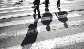 Sombree la silueta de una gente que cruza la calle Imagen de archivo