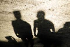 Sombreia silhuetas dos homens que estão na praça da cidade no bla do sepia imagens de stock