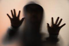 Sombreie o borrão do homem do horror no revestimento com capa mãos no vidro foto de stock