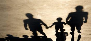 Sombreie a silhueta dos pais e do filho que guardam as mãos ao andar foto de stock
