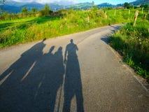 Sombreie uma silhueta de quatro povos em uma estrada no meio de um verde imagens de stock