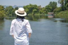 Sombrero asi?tico del desgaste de mujer y camisa blanca con la situaci?n en el puente de madera, ella que mira adelante al r?o, fotos de archivo