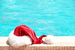 Sombrero auténtico de Santa Claus cerca de la piscina foto de archivo libre de regalías