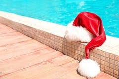 Sombrero auténtico de Santa Claus cerca de la piscina imágenes de archivo libres de regalías