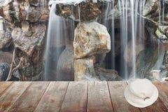 Sombrero blanco en piso de madera y fluir de la cascada Foto de archivo