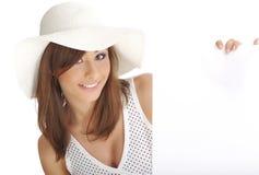 Sombrero blanco que desgasta de la mujer que lleva a cabo a la tarjeta en blanco. Imagen de archivo