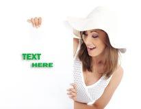 Sombrero blanco que desgasta de la mujer que lleva a cabo a la tarjeta en blanco. Imágenes de archivo libres de regalías