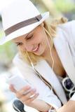 Sombrero blanco que lleva de la mujer joven y el escuchar la música Imagenes de archivo