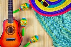 Sombrero coloreado la guitarra y los maracas en un fondo de madera Imagen de archivo libre de regalías