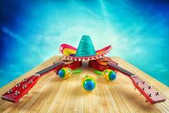 Sombrero coloreado la guitarra y los maracas en un fondo de madera Foto de archivo