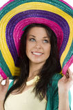 The sombrero colored. Portrait closeup of young and pretty brunette woman with colored big hat royalty free stock image