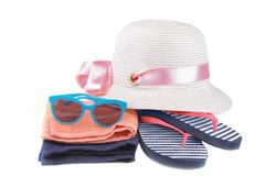 sombrero con chancletas en una tira azul y blanca al lado de una toalla anaranjada y azul y de vidrios azules Aislado fotos de archivo