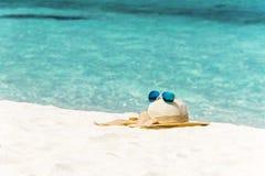 Sombrero con las gafas de sol en la playa Fotografía de archivo