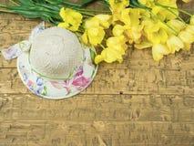 Sombrero con un ramo de tulipanes amarillos en una tabla de madera Imágenes de archivo libres de regalías