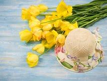 Sombrero con un ramo de tulipanes en una tabla de madera Imagenes de archivo