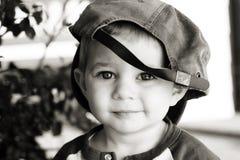 Sombrero de béisbol del muchacho que desgasta lindo Fotografía de archivo libre de regalías