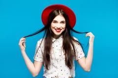 Sombrero de fieltro femenino rojo Aislado en fondo azul Feliz y fresco Fotos de archivo