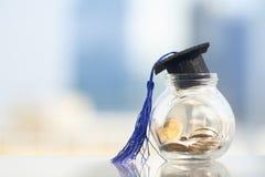 Sombrero de la graduación con la borla azul encima del tarro o de la hucha de cristal foto de archivo libre de regalías