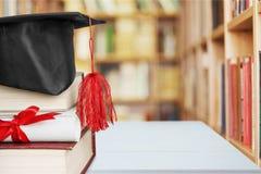 Sombrero de la graduación en la pila de libros y de diploma foto de archivo
